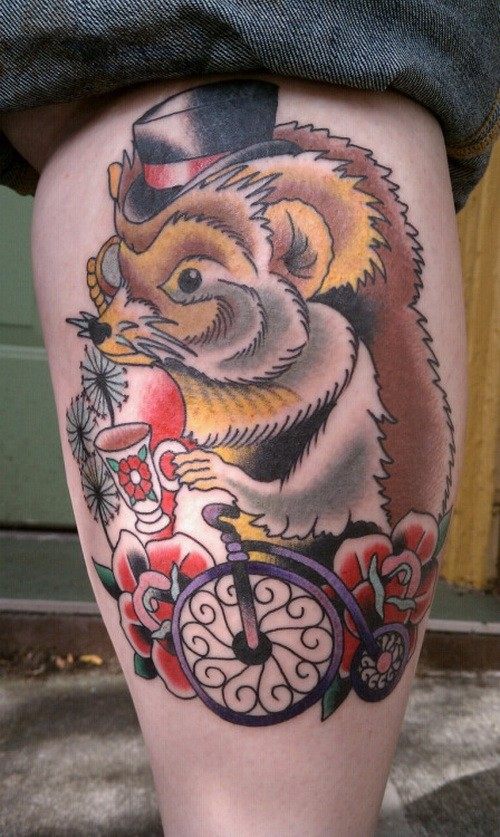Great old school colorful hedgehog in hat on bicycle tattoo on shin