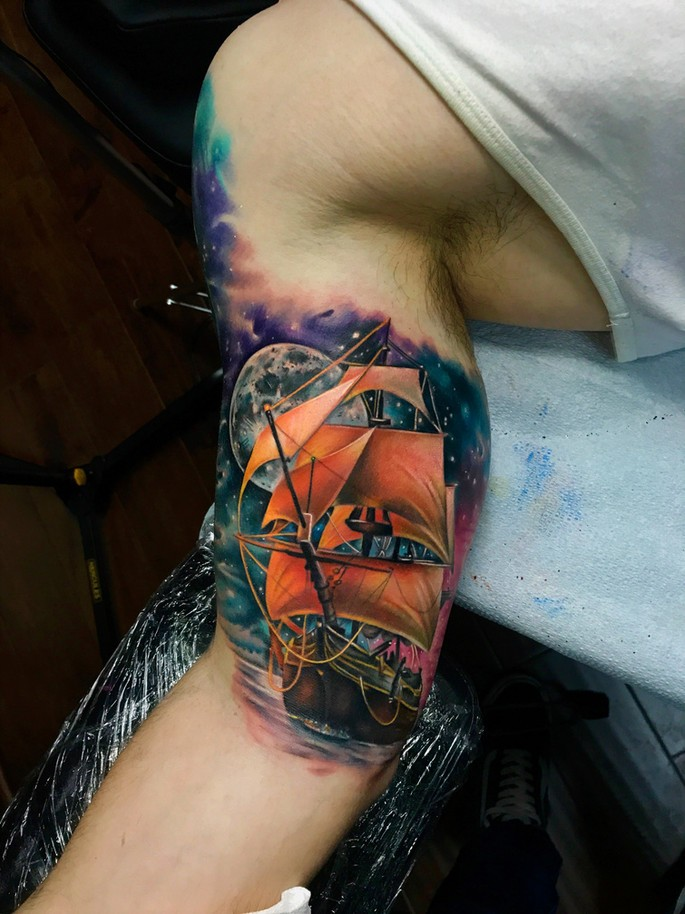 Great realistic ship in space tattoo on biceps