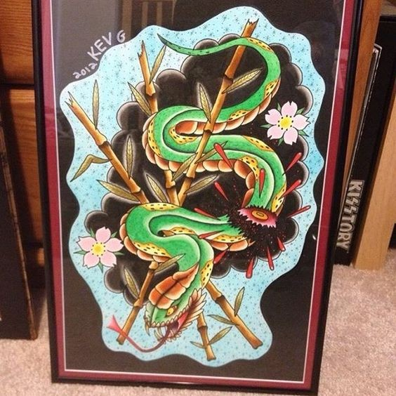 Green crawling reptile with bamboo and flower elements tattoo design