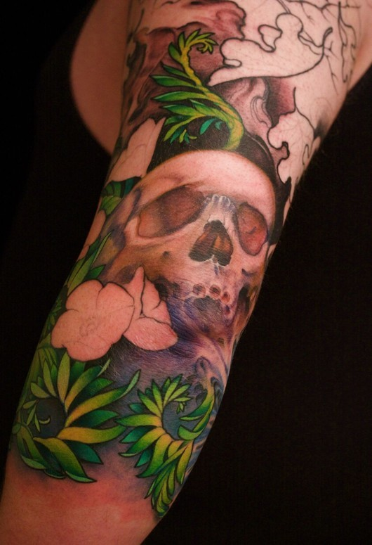 Green grass with skull tattoo on arm