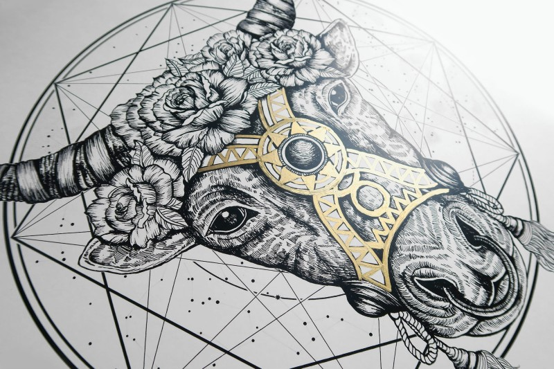Grey-ink bull head in floral wreath with gold decoration tattoo design