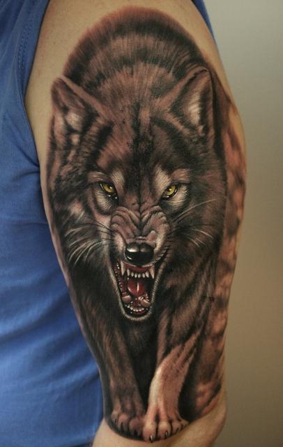Tatuaggio colorato sul deltoide il lupo con la bocca spalancata