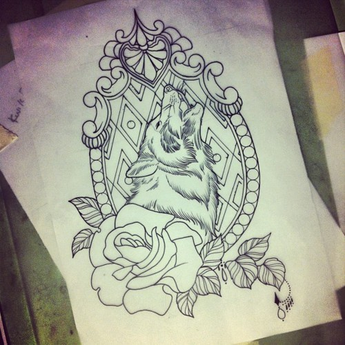 Howling wolf in decorated frame with a rose tattoo design