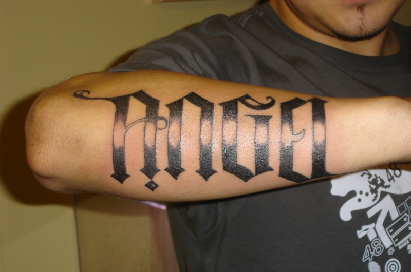 Huge-lettered angel word tattoo on forearm