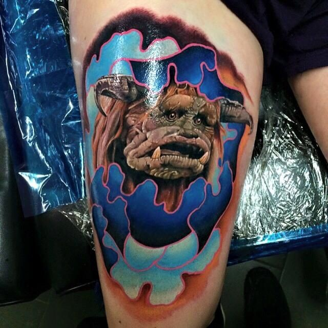 Illustrative style colored thigh tattoo of funny monster