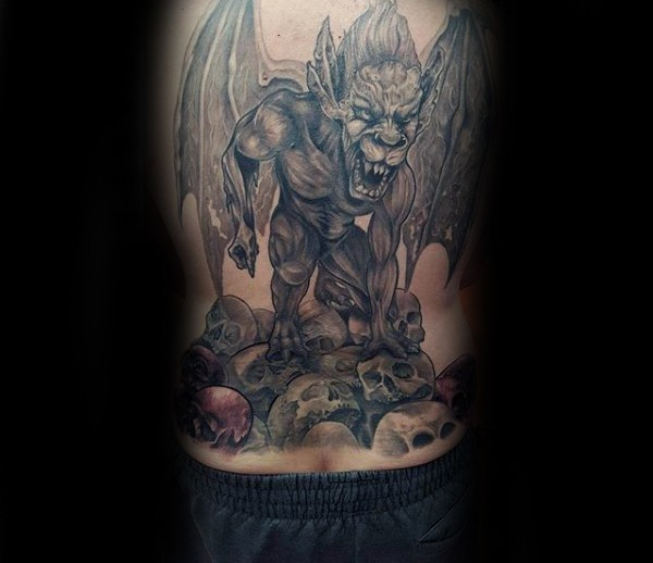 Illustrative style colored whole back tattoo of gargoyle sitting on human skulls