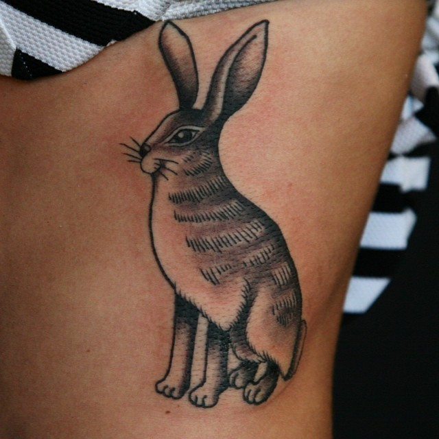 Interesting-designed black-and-white hare tattoo on side