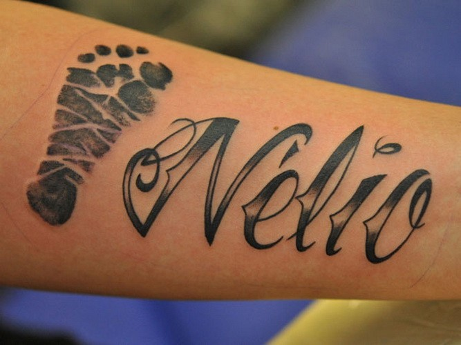 Interesting black name quote with foot print tattoo on arm