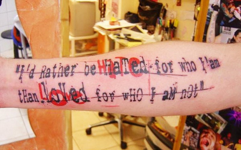 Interesting printed strikethrough black-and-red quote tattoo on forearm