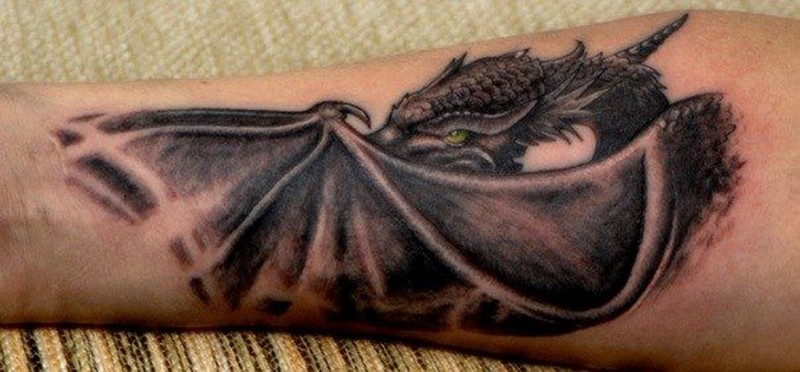 Large black green-eyed dragon tattoo on forearm