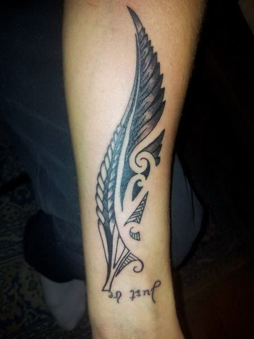 Large black tribal feather with quote tattoo on arm