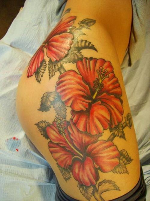 Large orange flowers tattoo on thigh