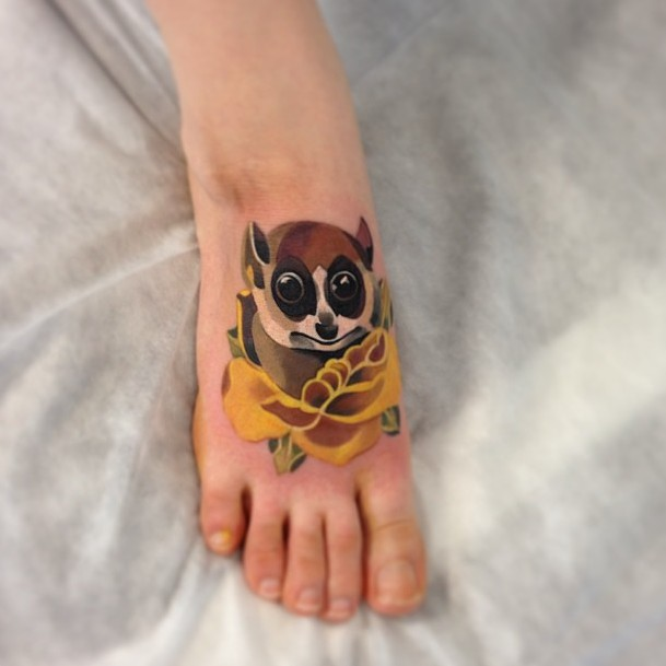 Little cute colorful lemur in yellow rose tattoo on foot
