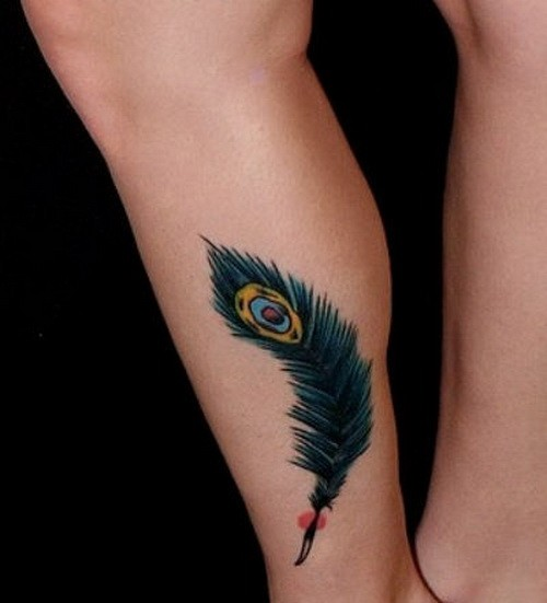 Little turquoise-colored peacock feather tattoo on shin