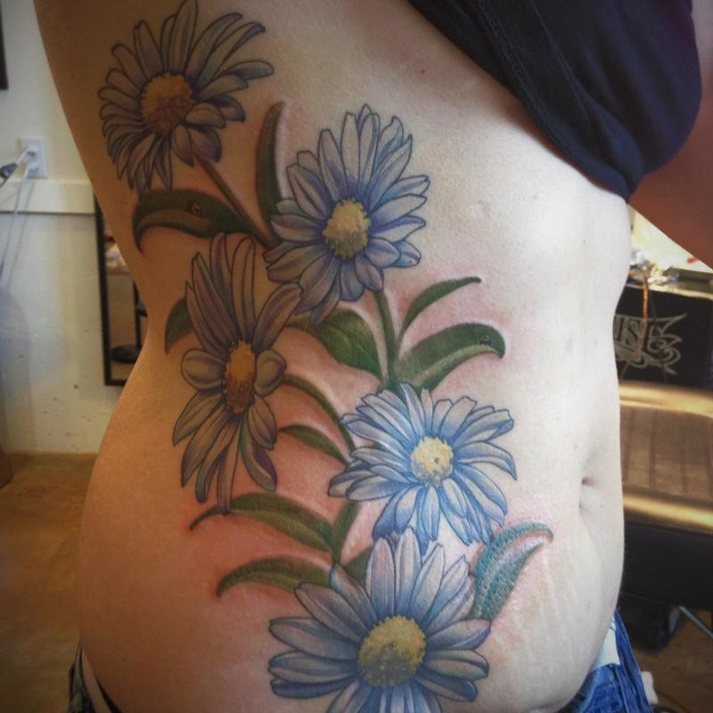 Lovely colorful daisy flowers tattoo on side