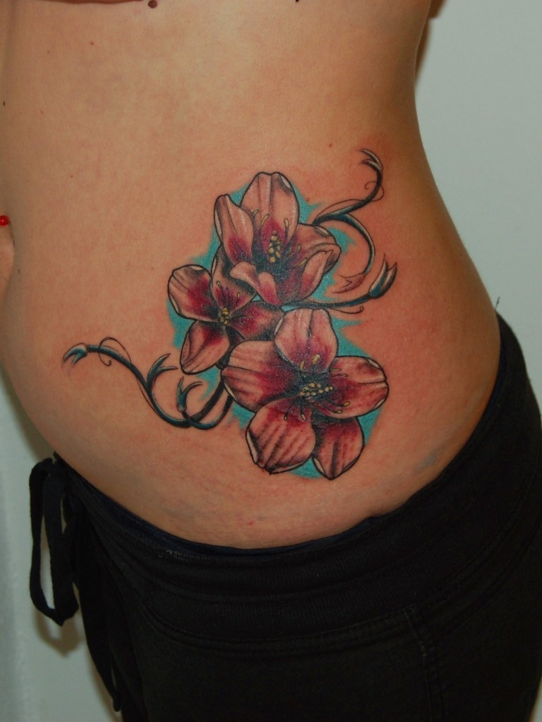 Lovely colorful exotic flowers tattoo on side