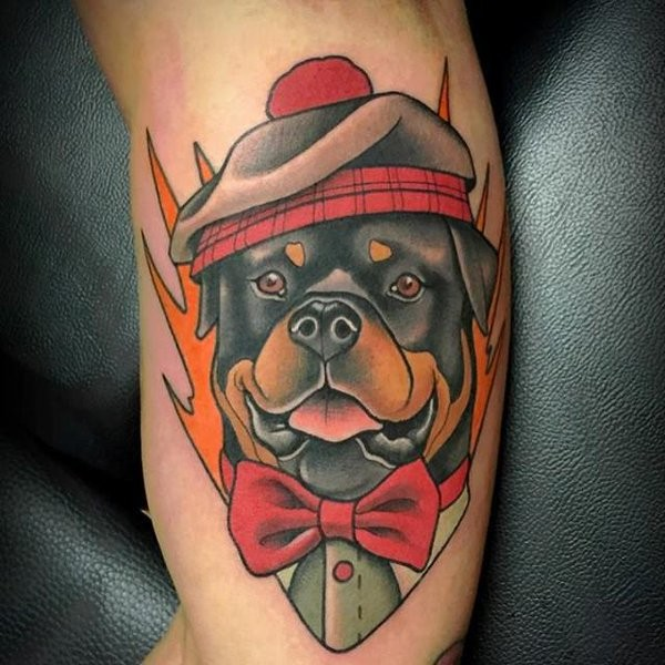 Lovely colorful rottweiler in cap and bow-tie tattoo on arm