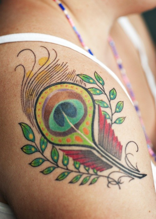 Lovely little colorful peacock feather tattoo for women on shoulder