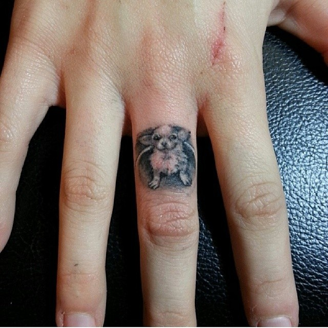 Lovely small black-and-white dog tattoo on finger