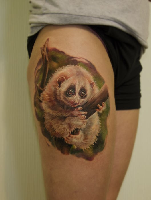 Lovely white lemur sitting on tree branch tattoo on thigh