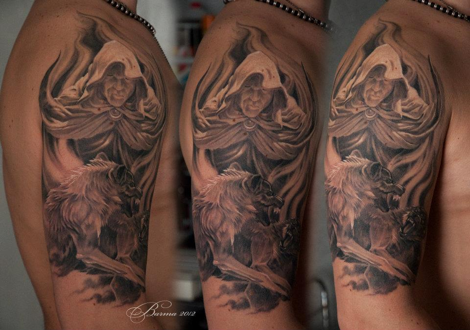 Man in hood with two wolves tattoo on shoulder