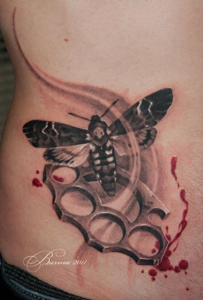 Tatuaggio di falena e tirapugni sul lato
