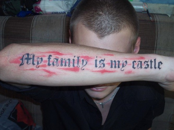 My family is my castle quote on red background tattoo on arm