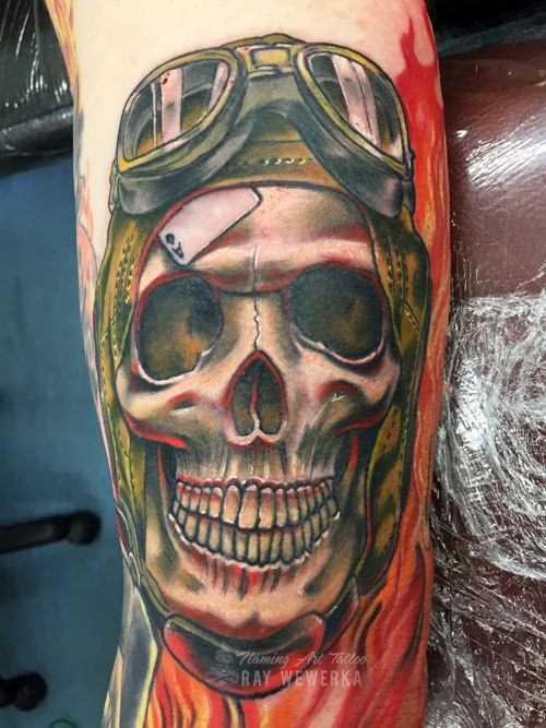New school style colored biceps tattoo of smiling pilot skull in helmet