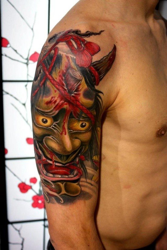 New school style upper arm tattoo of monster face with red rope