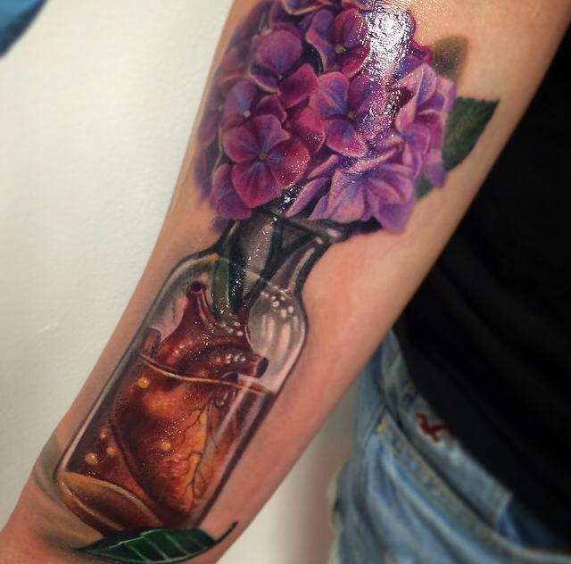 Nice flowers and heart in bottle tattoo