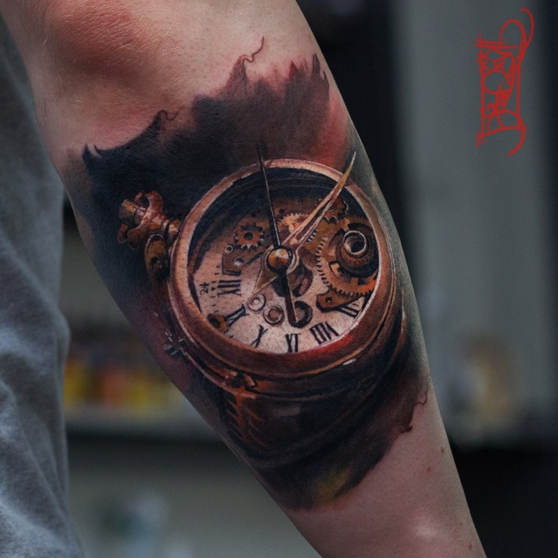 Old clock tattoo on forearm