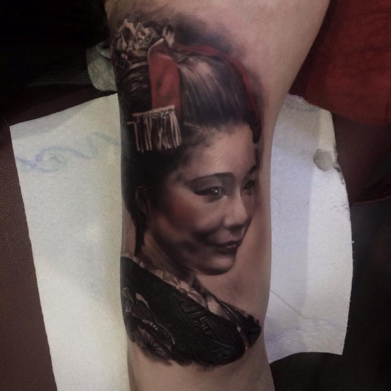 Old looking colored upper arm tattoo of geisha portrait