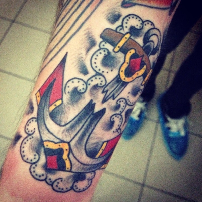 Old school anchor in clouds tattoo on forearm