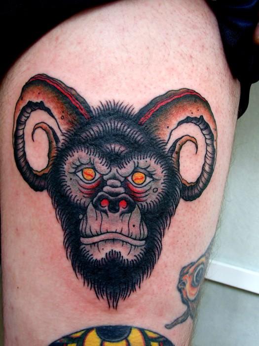 Old school color-ink horned devil gorilla tattoo on thigh