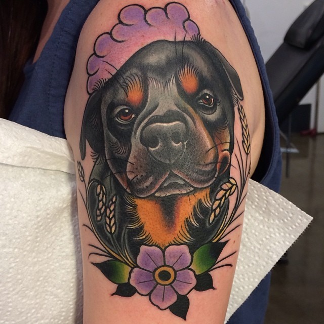 Old school rottweiler with flower tattoo on upper arm