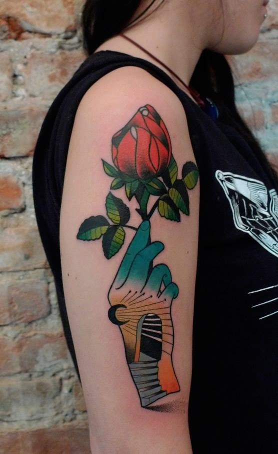 Old school style colored upper arm tattoo or green hand with rose