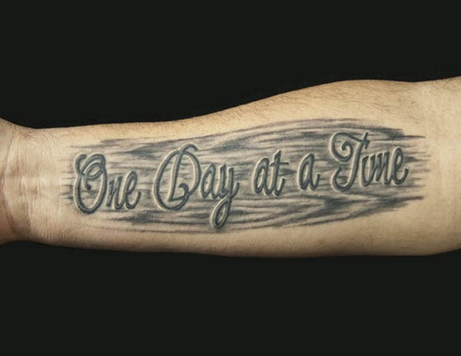 One Day At A Time Quote On Black Background Tattoo On Arm