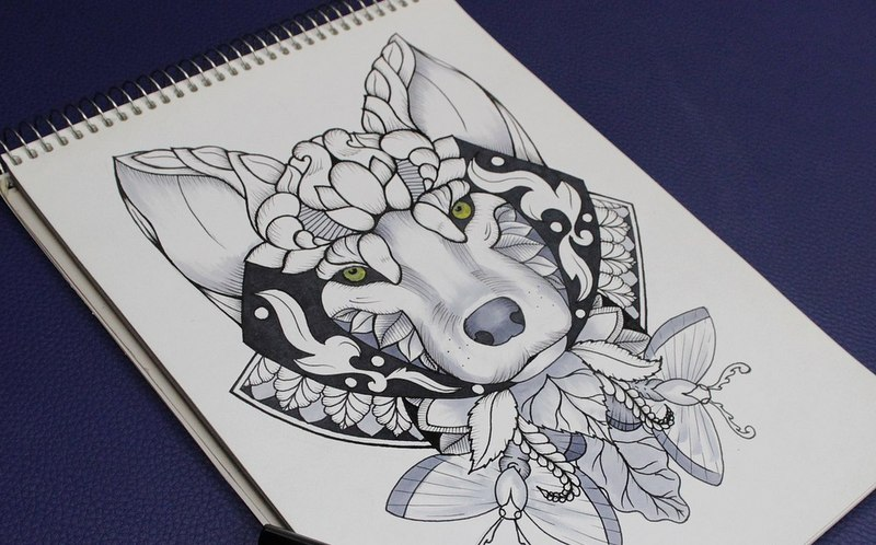 Ornamented green-eyed wolf head with mothes tattoo design