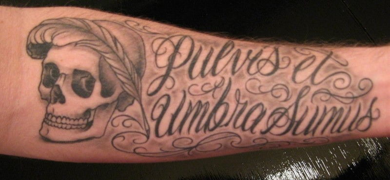 Ornate-lettered quote with scull and feather tattoo on arm