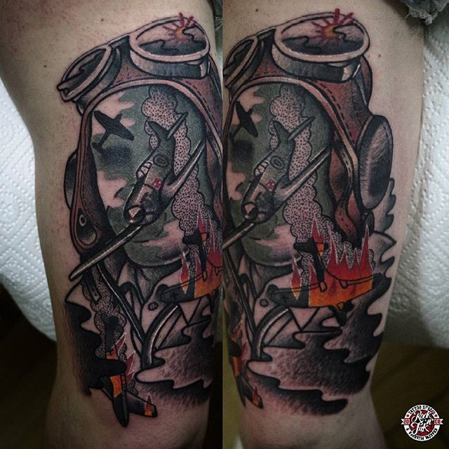 Psyhedelic style colored biceps tattoo of pilot with burning planes