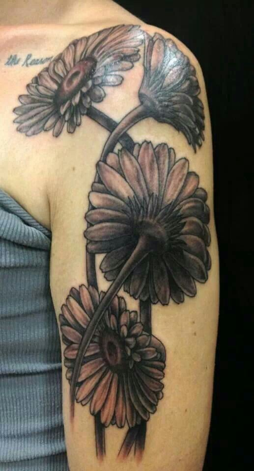 Realistic black-and-white daisy flowers tattoo on upper arm