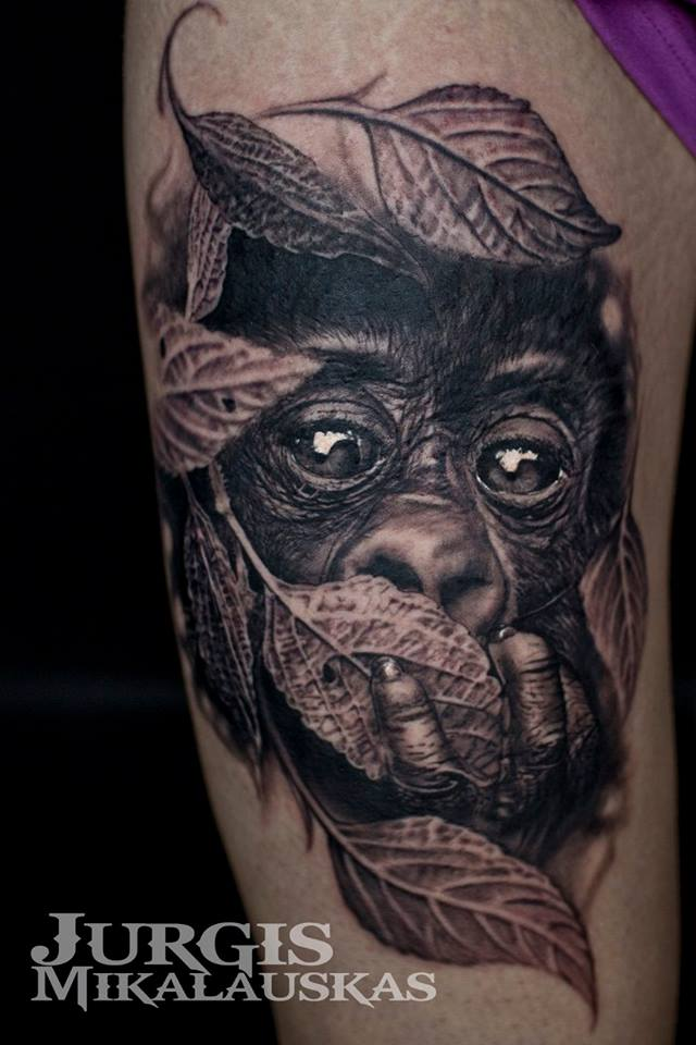 Realistic cute little chimpanzee in leafs tattoo