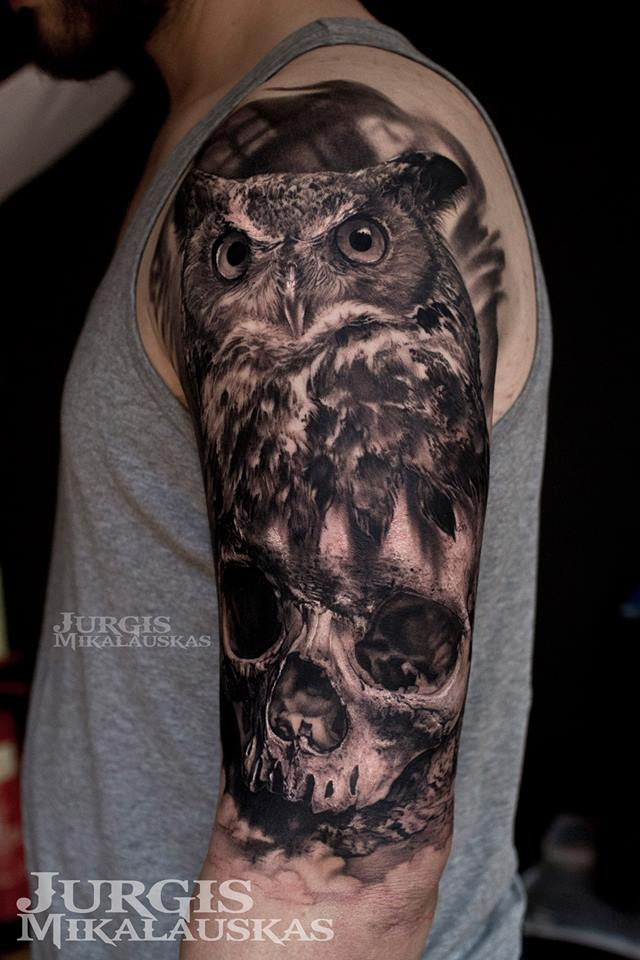 Realistic owl and skull tatto on shoulder