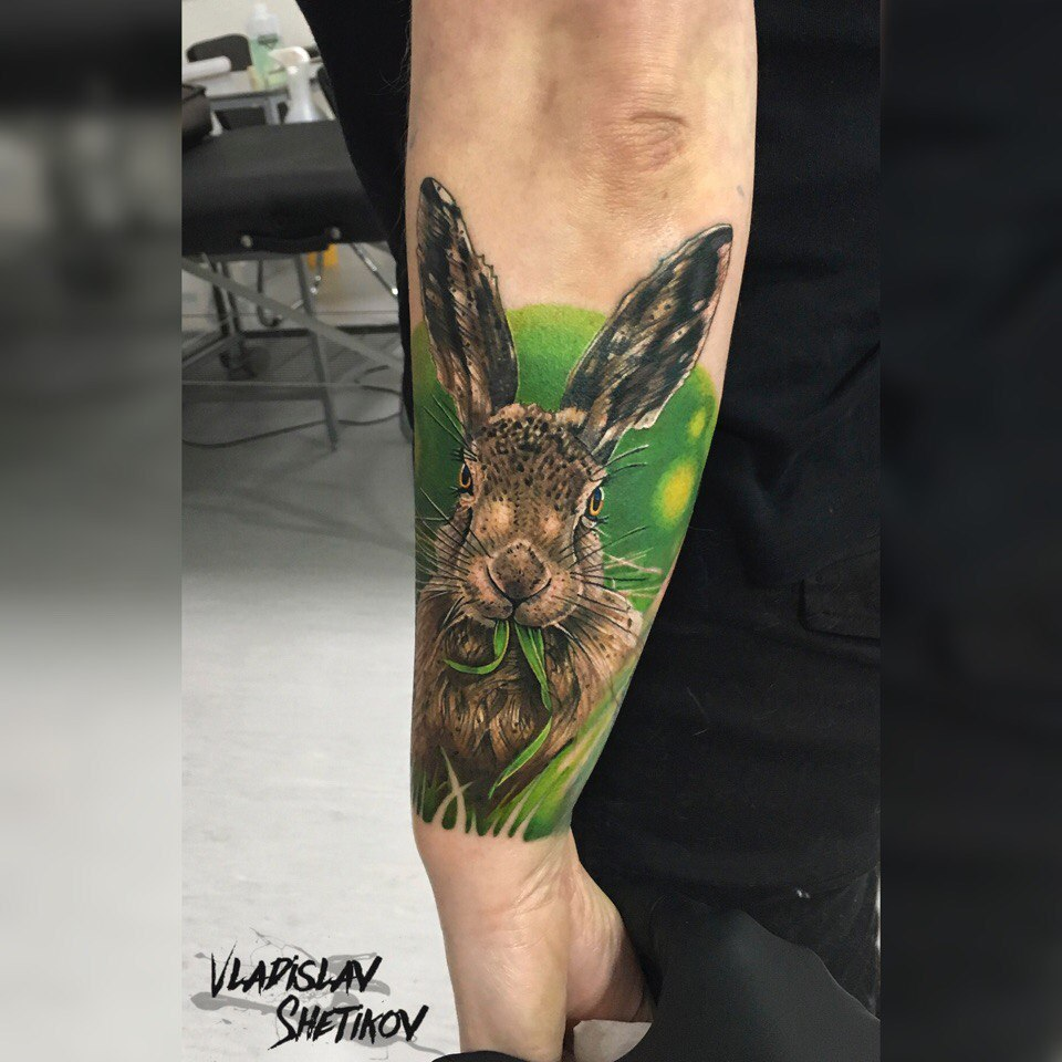 Realistic rabbit in grass tattoo on forearm