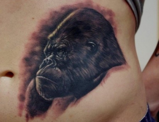 Realistic severe black-ink gorilla tattoo on belly