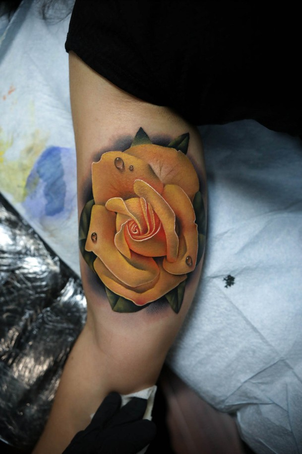 Realistic yellow rose tattoo on biceps