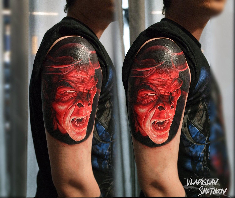 Red demon face tattoo on shoulder