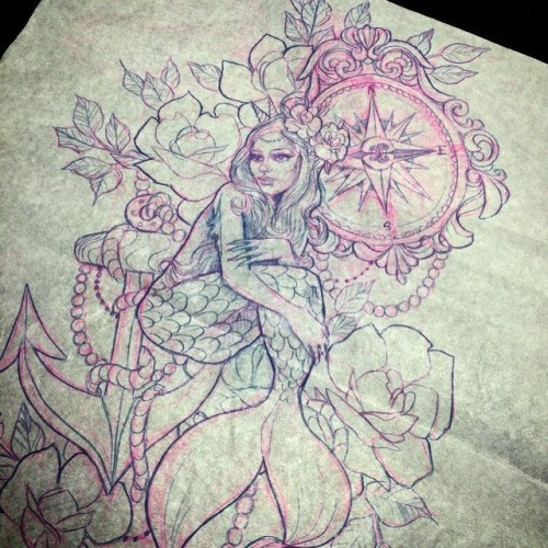 Sad sitting mermaid surrounded with flowers and huge compass tattoo design