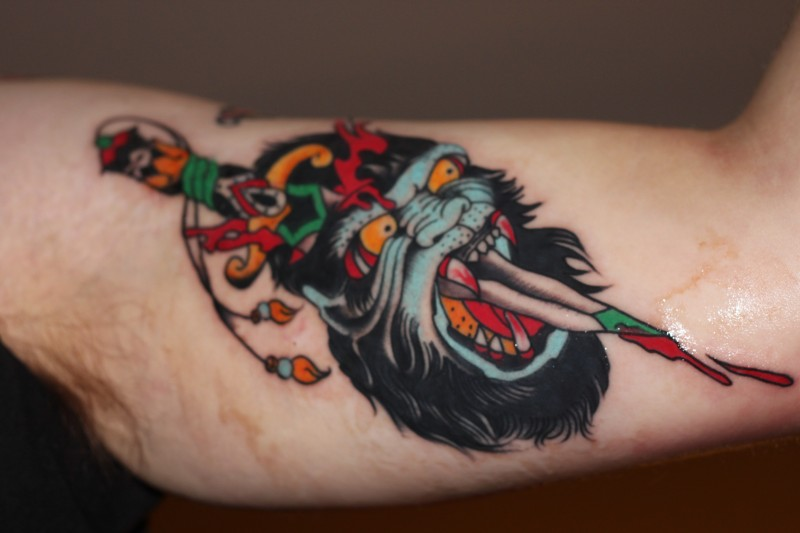 Scary old school color-ink gorilla head pierced by knife tattoo on upper arm