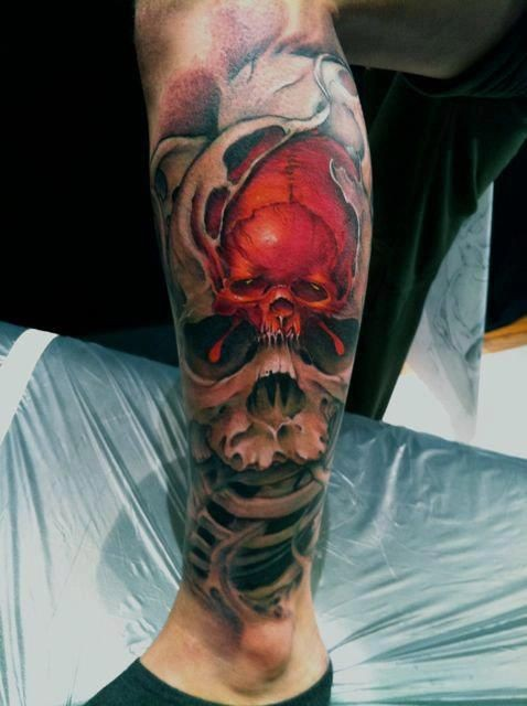Scary red black skull tattoo on leg